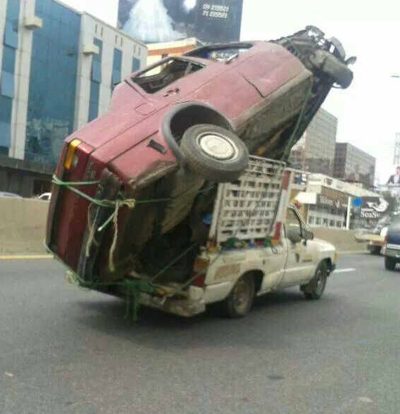 Photo of a small truck overloaded with a bigger pick-up truck in its box