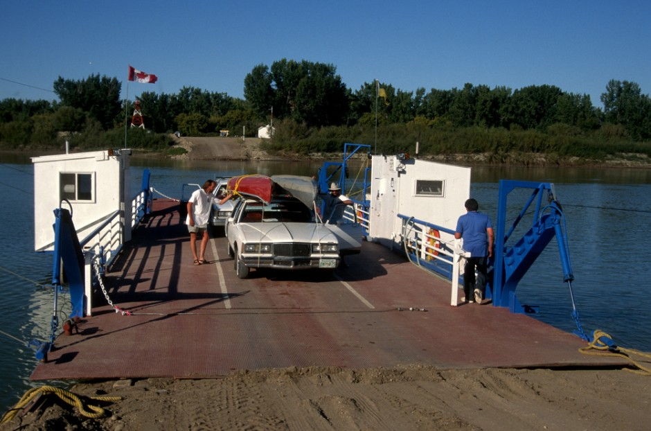Canoe and car riding the Estuary Ferry across the South Saskatchewan River.