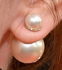 A pearl bubble earring shown with the large pearl to the back of the ear and the smaller pearl to the front.